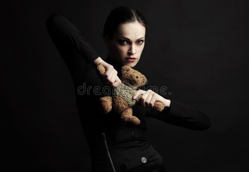 La mujer de Vogue en vestido negro sostiene un oso del juguete imágenes de archivo libres de regalías