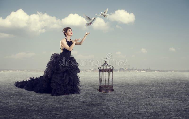 La mujer deja los pájaros hacia fuera fotografía de archivo
