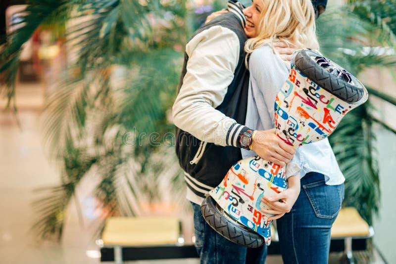 La mujer del abd del hombre que abraza después de novio da el hoverboard del regalo para su novia imagen de archivo