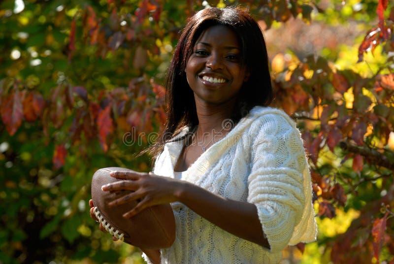 La mujer del African-American lleva a cabo el balompié foto de archivo