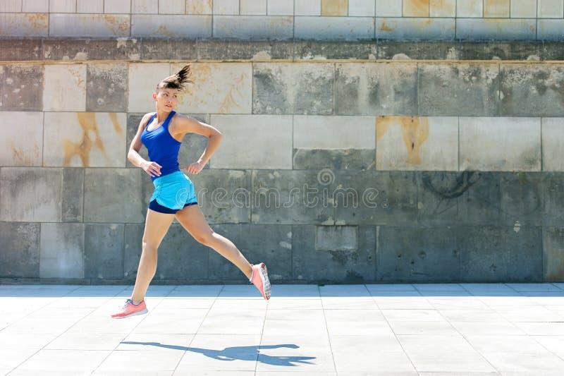 La mujer del basculador salta por la pared en ciudad Mire detrás foto de archivo libre de regalías