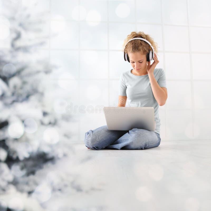 La mujer del concepto de la Feliz Navidad en el ordenador con los auriculares que hojea Internet escucha la música o ve una pelíc fotos de archivo