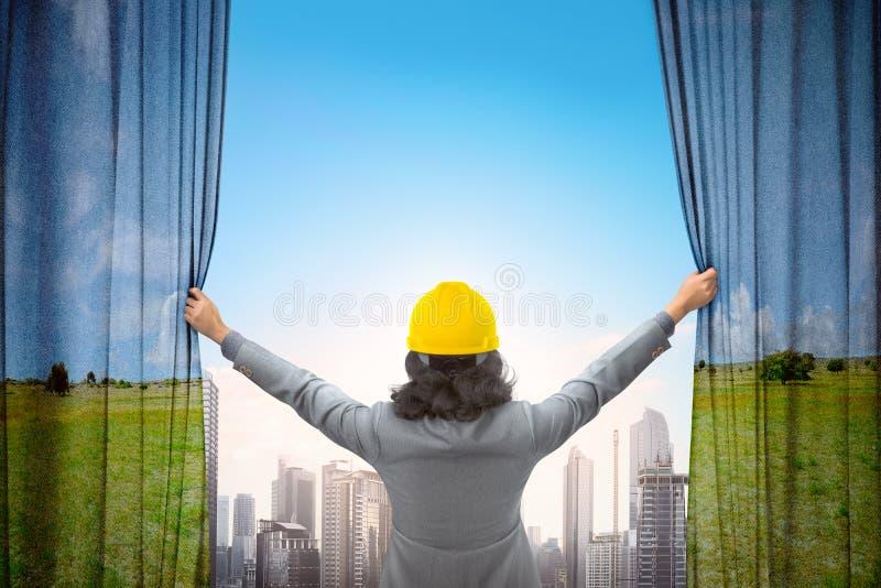 La mujer del contratista abre la cortina del paisaje y el cityscap de la mirada imagen de archivo libre de regalías