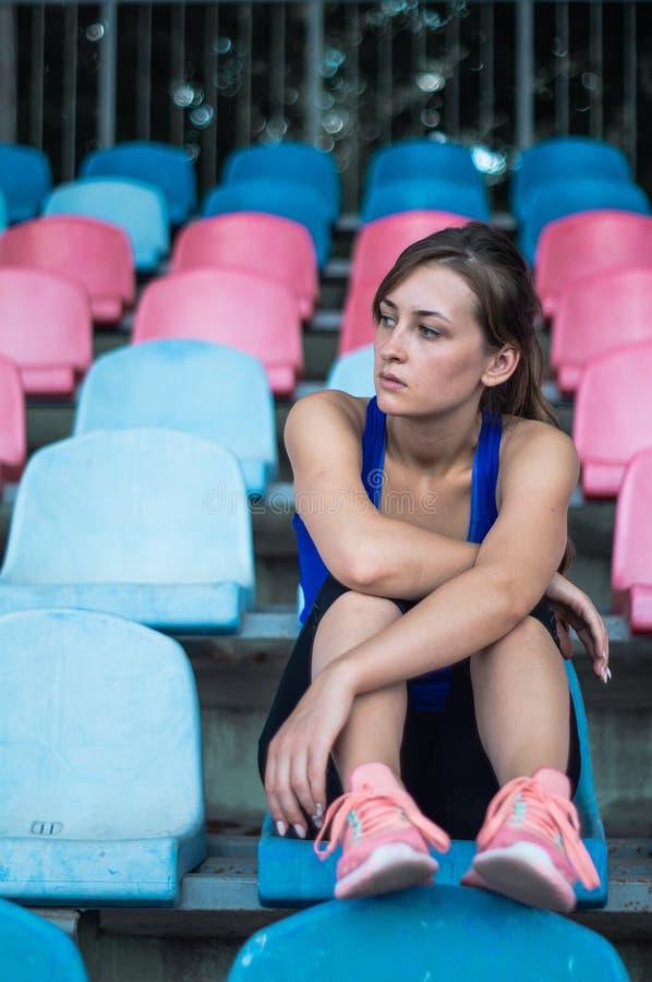 La mujer del deporte de la aptitud en ropa de deportes de la moda, se sienta mirando a las muchachas de funcionamiento de los dep fotografía de archivo