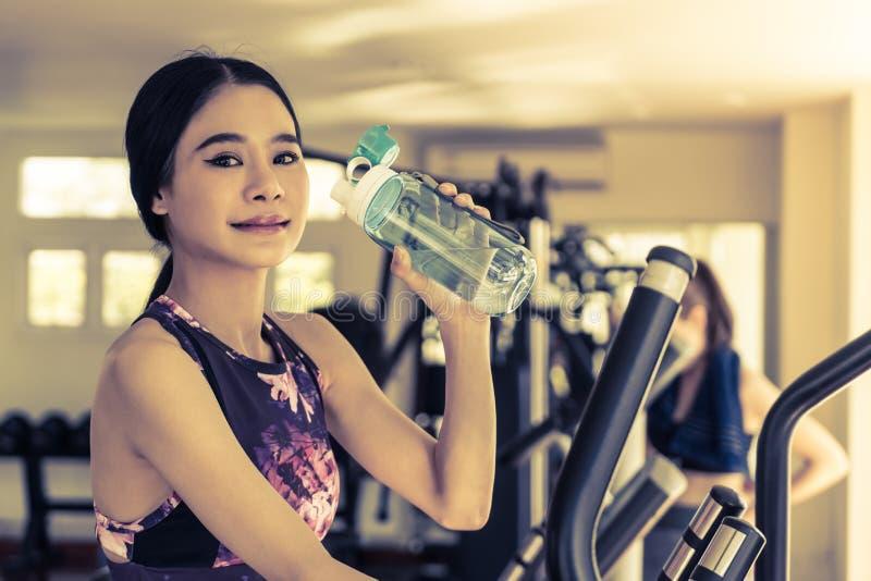 La mujer del deporte es agua potable en gimnasio de la aptitud fotos de archivo