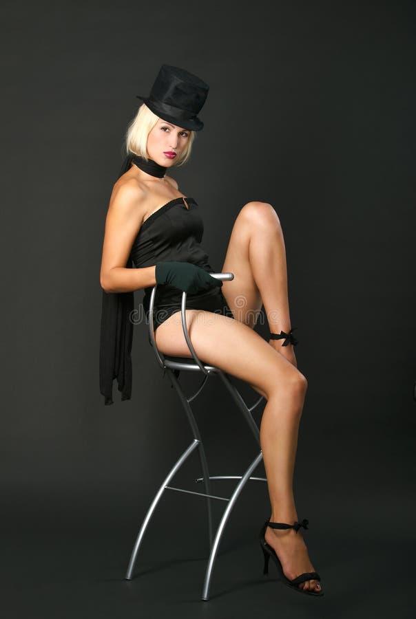 La mujer del espectáculo de variedades se está sentando en silla de la barra. fotografía de archivo