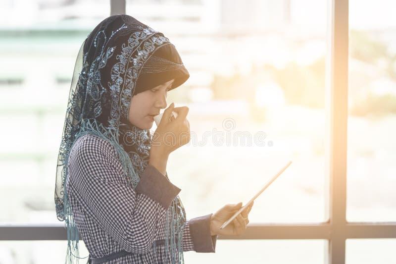 La mujer del Islam está bebiendo el café mientras que mira la tableta imagenes de archivo