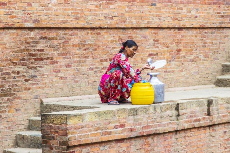 La mujer del Nepali llena el agua imagen de archivo libre de regalías