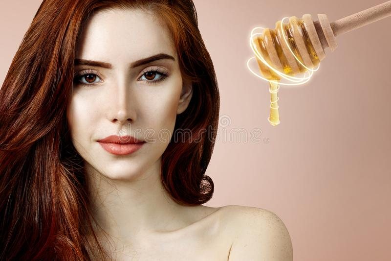 La mujer del pelirrojo y la cuchara jovenes de la miel se preparan para la máscara facial imagen de archivo libre de regalías