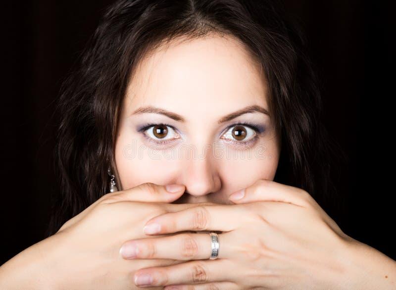 La mujer del primer mira derecho en la cámara en un fondo negro Ella cubrió su boca con su mano expresa imagenes de archivo
