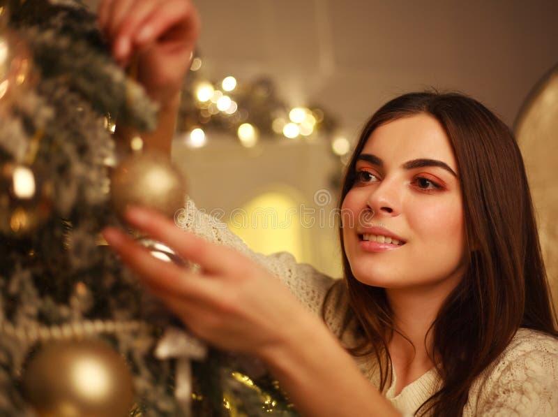 La mujer del primer que adorna el ` s del Año Nuevo del árbol de navidad juega en casa fotos de archivo libres de regalías