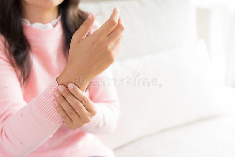 La mujer del primer que se sienta en el sofá lleva a cabo su lesión de mano de la muñeca foto de archivo