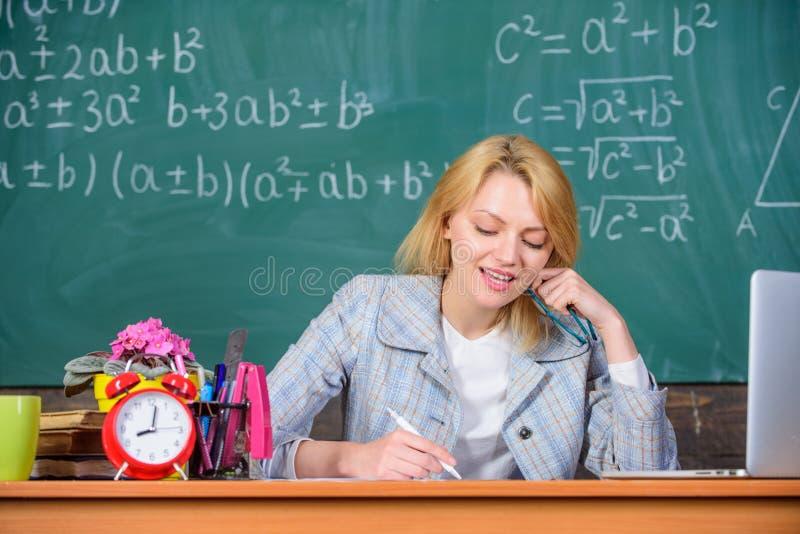 La mujer del profesor sienta el fondo de la pizarra de la tabla Communicability excelente y habilidades interpersonales Pozo orga fotos de archivo