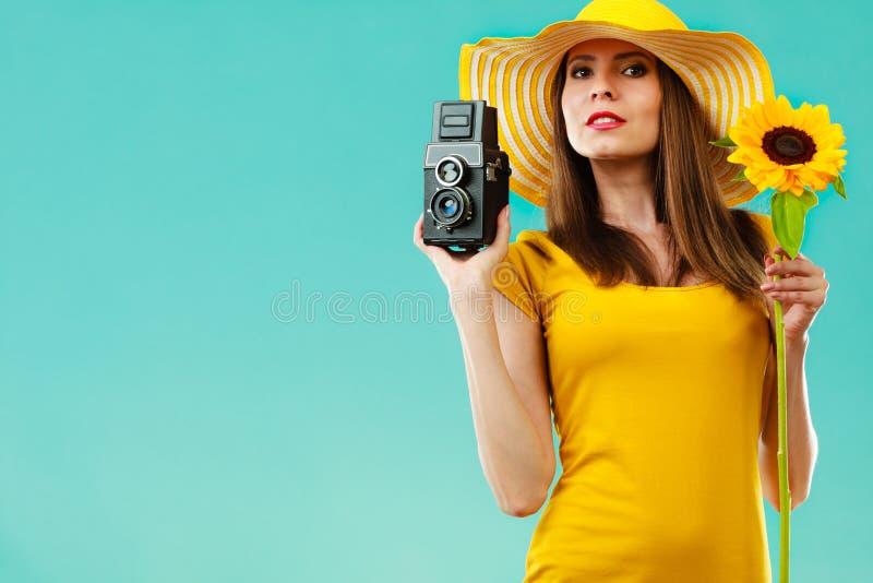 La mujer del verano sostiene la c?mara vieja del girasol fotografía de archivo