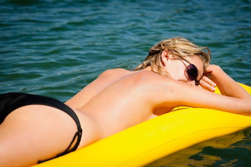 La mujer del verano toma el sol en el colchón flotante del agua fotos de archivo libres de regalías