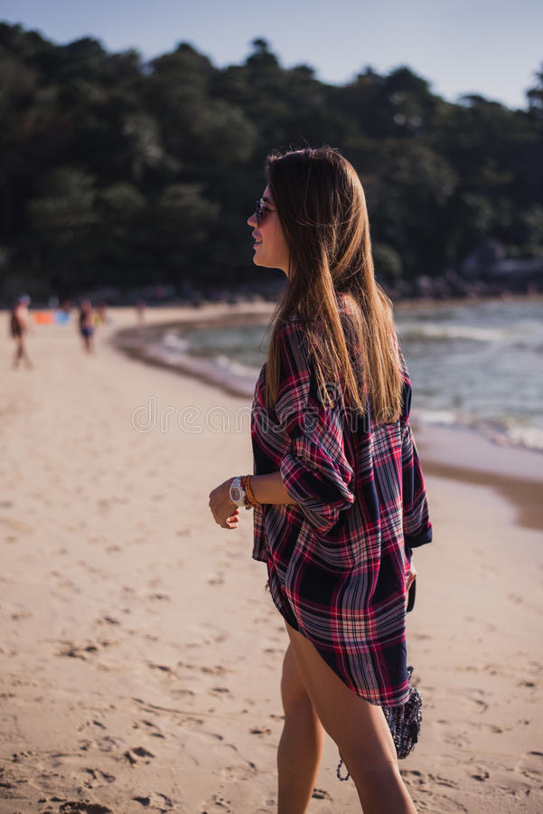 La mujer delgada hermosa en camisa, los pantalones cortos y las gafas de sol de la moda caminan en la playa Visión desde la parte fotos de archivo