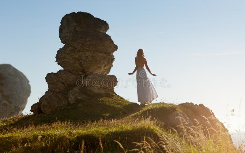 La mujer delgada hermosa en el vestido largo blanco se coloca al lado de una formación de roca extraña en Irlanda imagen de archivo