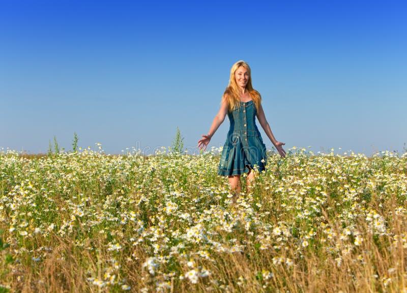 La mujer delgada joven con un pelo justo largo en los sundress azules alegre se mueve en el campo de camomiles contra el cielo azu imágenes de archivo libres de regalías