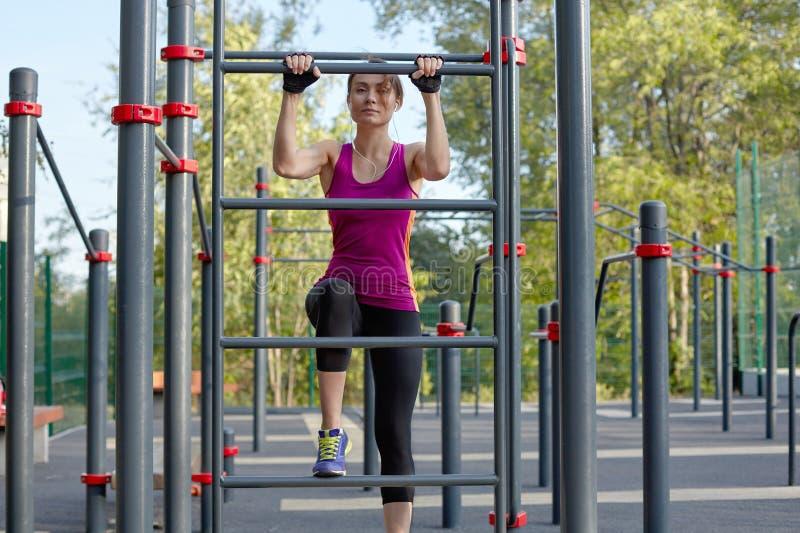 La mujer delgada joven hermosa en ropa de deportes brillante sube para arriba en la escalera en el sportsground al aire libre fotografía de archivo