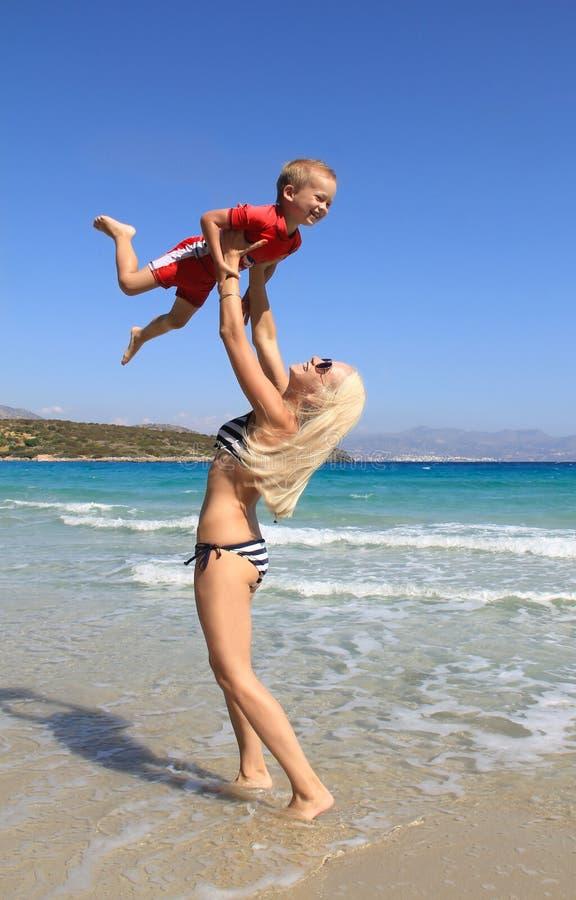 La mujer delgada joven lanza para arriba y coge a su poco hijo en la playa por el mar azul claro La madre y su pequeño bebé lindo imagen de archivo libre de regalías