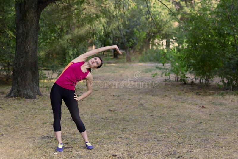 La mujer delgada joven magnífica hace el gimnasio en parque de la mañana Inclinación lateral, ropa de deportes brillante, auricul imagenes de archivo