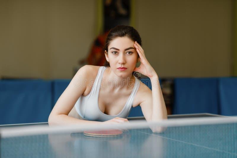 La mujer delgada presenta en la tabla de ping-pong dentro foto de archivo