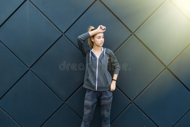 La mujer deportiva con la figura perfecta y las nalgas que estiraban sus brazos contra la pared con el espacio de la copia para s imagen de archivo libre de regalías