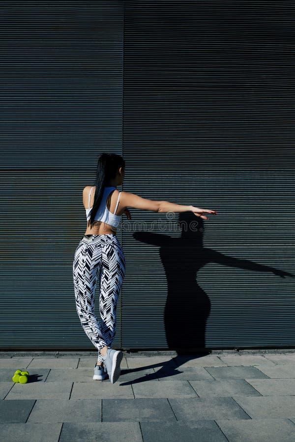 La mujer deportiva con la figura perfecta y las nalgas forman el ejercicio contra la pared con el espacio de la copia para su men fotografía de archivo libre de regalías