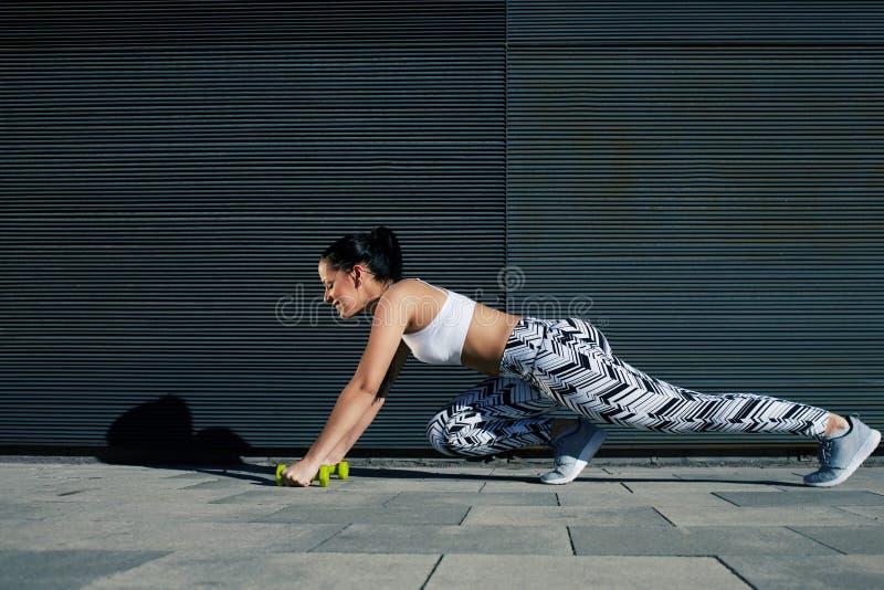 La mujer deportiva con la figura perfecta y las nalgas forman estirar las piernas con pesas de gimnasia cerca de la pared del esp imagenes de archivo