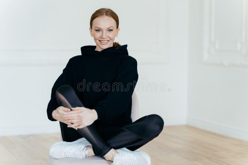 La mujer deportiva europea positiva en buen humor tiene componer, sienta las piernas cruzadas en silla cómoda, tiene expresión al imagen de archivo