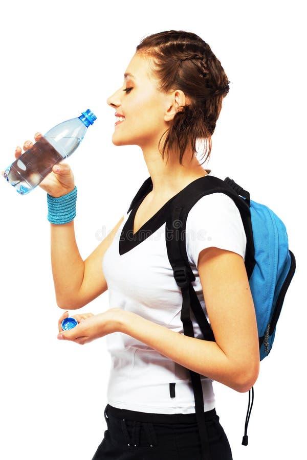 La mujer deportiva feliz está bebiendo un agua dulce imagen de archivo