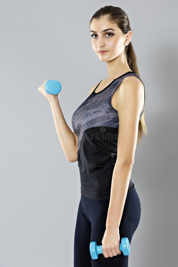 La mujer deportiva hace su entrenamiento con las pesas de gimnasia, aisladas en el CCB gris imagen de archivo