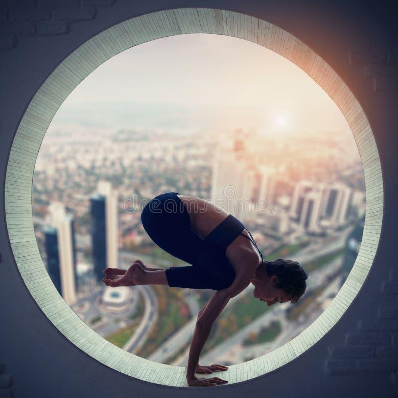 La mujer deportiva hermosa de la yogui del ajuste practica el asana Bakasana de la yoga - crane la actitud en una ventana redonda fotos de archivo libres de regalías