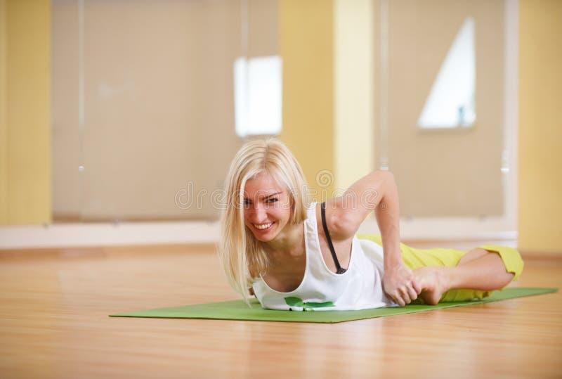La mujer deportiva hermosa de la yogui del ajuste practica el asana Bhekasana - actitud de la yoga de la rana en el cuarto de la  fotografía de archivo