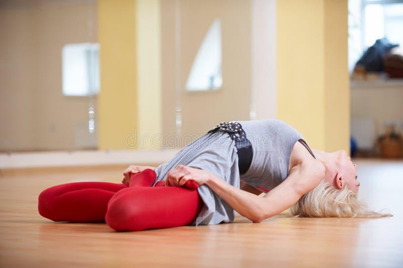 La mujer deportiva hermosa de la yogui del ajuste practica el asana Matsyasana de la yoga - pesque la actitud en el cuarto de la  imagen de archivo libre de regalías