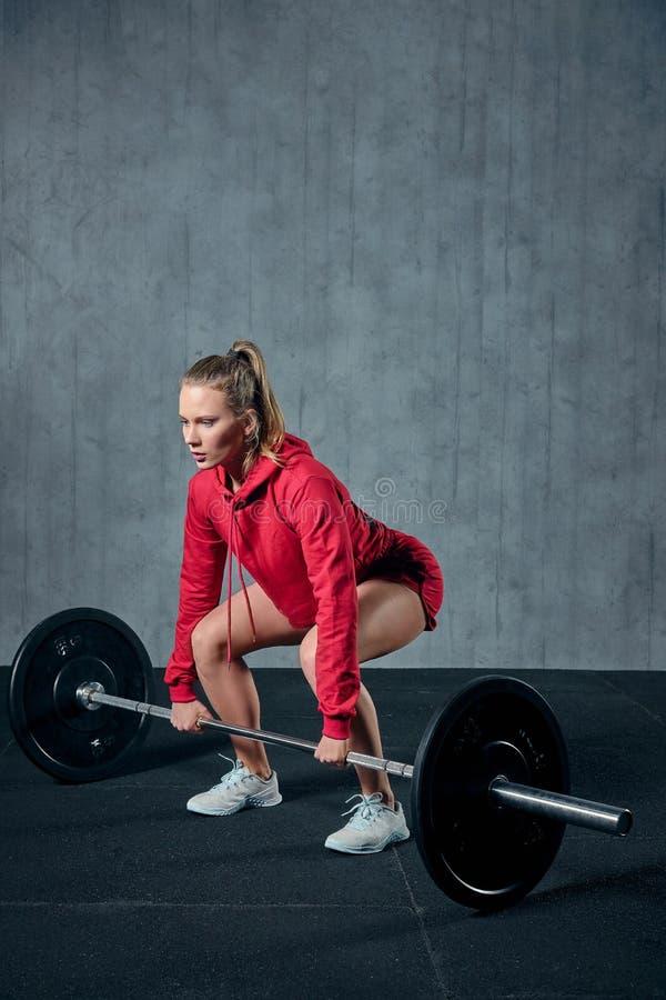 La mujer deportiva joven atractiva se está resolviendo en gimnasio La mujer muscular se está poniendo en cuclillas con el barbell fotografía de archivo libre de regalías