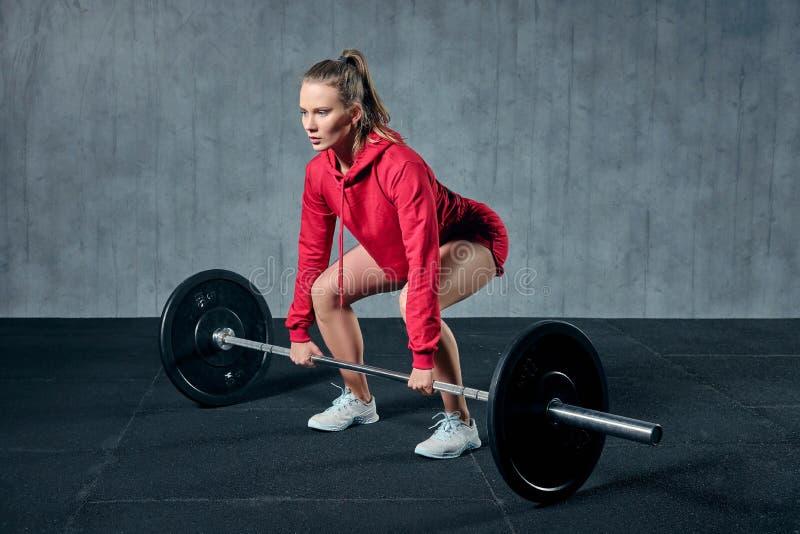 La mujer deportiva joven atractiva se está resolviendo en gimnasio La mujer muscular se está poniendo en cuclillas con el barbell foto de archivo libre de regalías