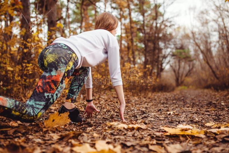La mujer deportiva joven de Concentrared está lista para correr al aire libre en el parque del otoño foto de archivo libre de regalías