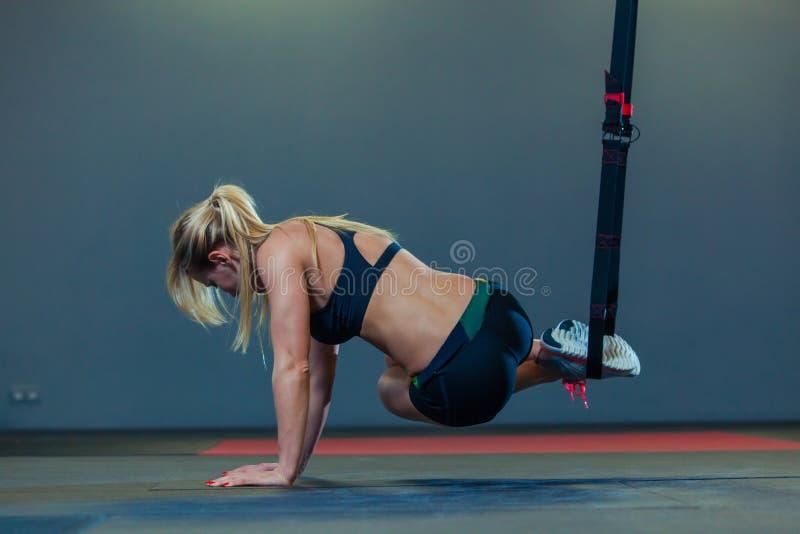 La mujer deportiva que hace TRX ejercita en el gimnasio foto de archivo libre de regalías