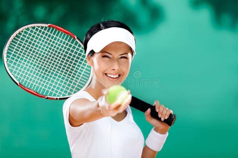 La mujer deportiva sirve la pelota de tenis foto de archivo libre de regalías