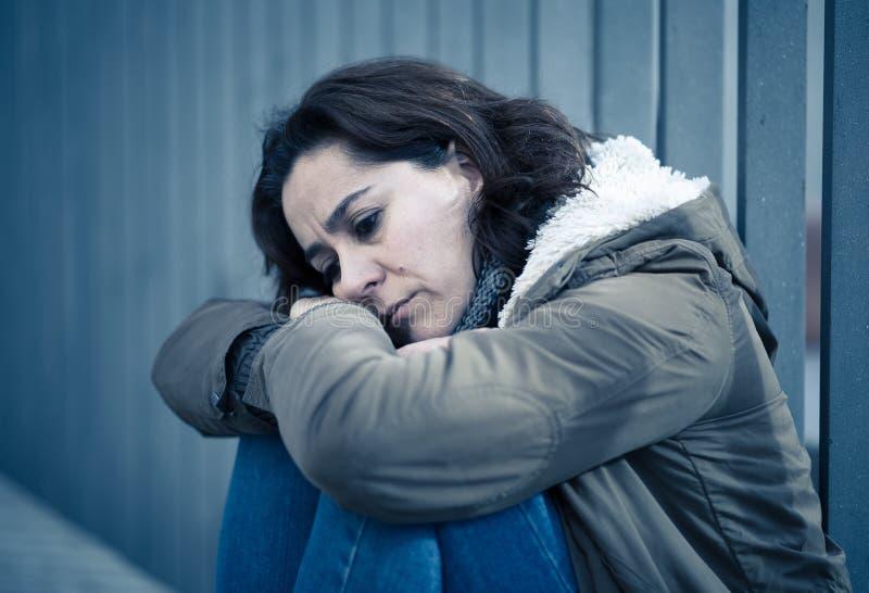 La mujer deprimida que se sentaba en la calle urbana de la ciudad abrum? y salta fotos de archivo