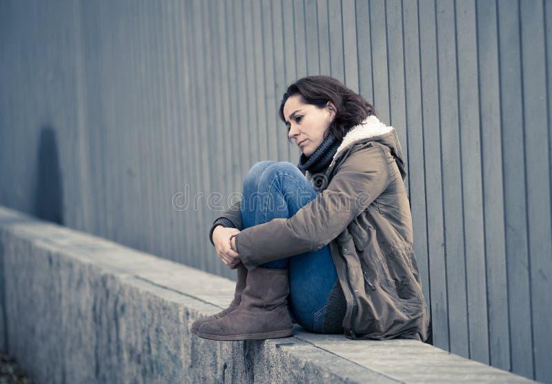 La mujer deprimida que se sentaba en la calle urbana de la ciudad abrum? y salta imagen de archivo libre de regalías