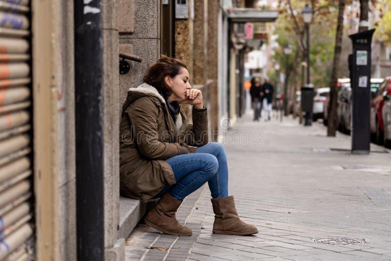 La mujer deprimida que se sentaba en la calle urbana de la ciudad abrum? y salta imágenes de archivo libres de regalías