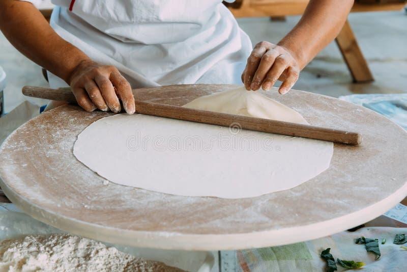 La mujer desarrolla la pasta, tortas planas tradicionales turcas imágenes de archivo libres de regalías