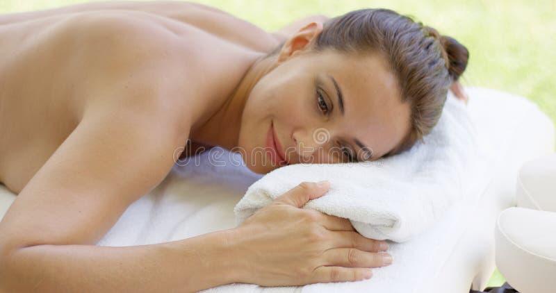La mujer desnudada pone el vientre abajo en la tabla foto de archivo