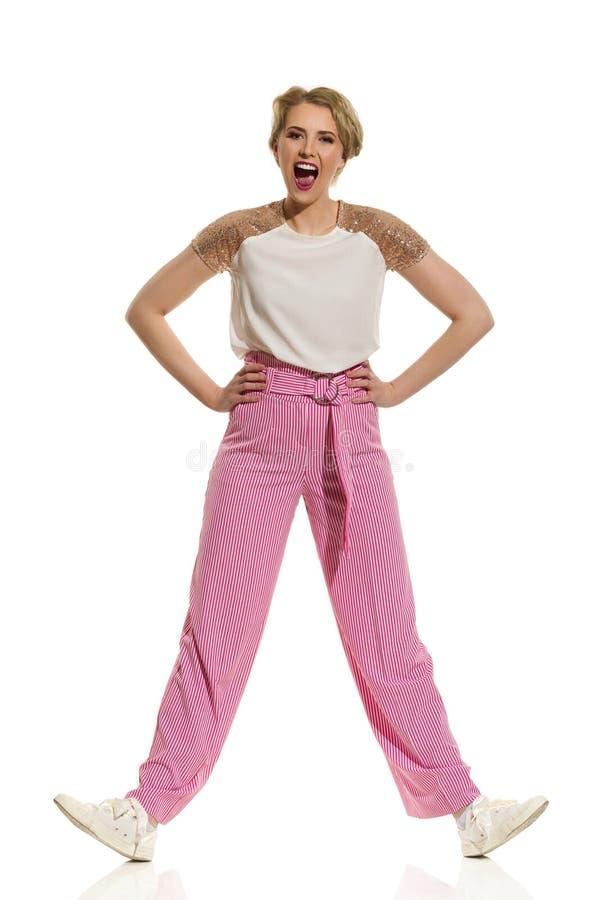 La mujer despreocupada en pantalones anchos rayados de las piernas se est? manteniendo aparte las piernas y el grito foto de archivo