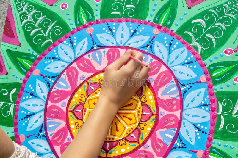 La mujer dibuja una mandala, mano con un primer del cepillo ilustración del vector