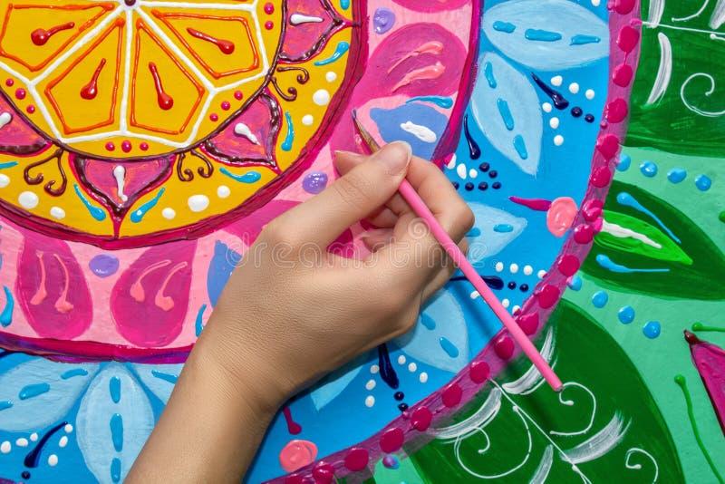 La mujer dibuja una mandala, mano con un primer del cepillo imágenes de archivo libres de regalías