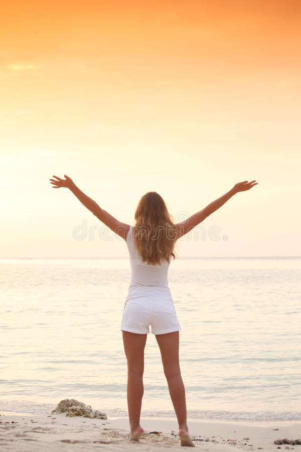 La mujer disfruta de puesta del sol sobre el mar imagenes de archivo