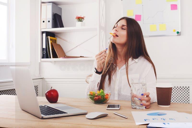 La mujer disfruta del almuerzo de negocios sano en interior moderno de la oficina fotos de archivo